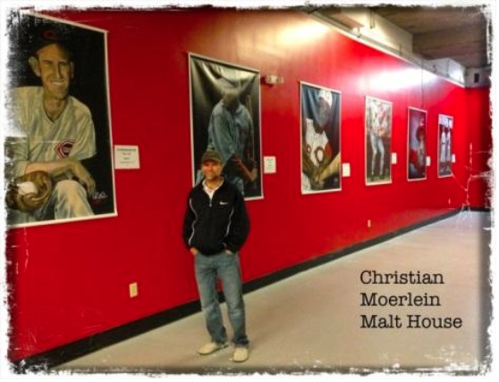 Chris Felix stands in front of several of his hand-painted prints depicting Cininnati Reds ballplayers at a recent exhibit.